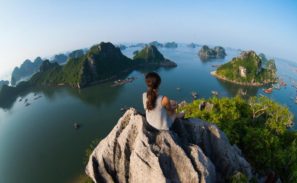 Junge Frau sitzt auf einem Hügel in der Natur und sinniert über ihre nächsten Reisen, die sie anstreben wird